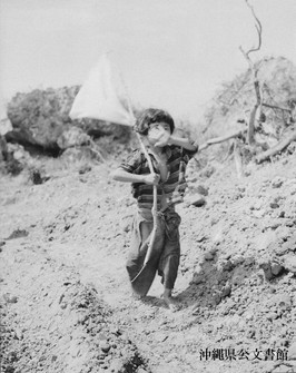 A young girl surrenders with a white flag. (Photo courtesy of the Okinawa Prefectural Archives)