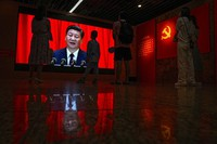 Visitors watch a screen showing Chinese President Xi Jinping speaking next to a Communist Party flag, in Beijing on Sunday, June 20, 2021. Authorities are gearing up to mark the 100th anniversary of the founding of China's ruling Communist Party, which will be observed on July 1. (AP Photo/Andy Wong)