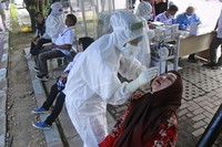 A medical worker collects nasal swab sample from a woman to be tested for coronavirus during a COVID-19 screening at University of North Sumatra in Medan, Indonesia, on June 21, 2021. (AP Photo/Binsar Bakkara)