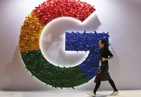 In this Nov. 5, 2018 file photo, a woman walks past the logo for Google at the China International Import Expo in Shanghai. (AP Photo/Ng Han Guan)