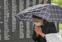 A woman prays before the Cornerstone of Peace, which commemorates the lives of people who died in the Battle of Okinawa during the Pacific War, at Okinawa Peace Memorial Park in the city of Itoman, Okinawa Prefecture, on June 23, 2021. (Mainichi/Yoshiyuki Hirakawa)