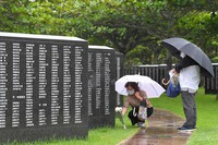 People offer flowers before the Cornerstone of Peace, which commemorates the lives of people who died in the Battle of Okinawa during the Pacific War, at Okinawa Peace Memorial Park in the city of Itoman, Okinawa Prefecture, on the morning of June 23, 2021. (Mainichi/Yoshiyuki Hirakawa)