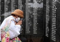 A woman prays for a relative before the Cornerstone of Peace, which commemorates the lives of people who died in the Battle of Okinawa during the Pacific War, at Okinawa Peace Memorial Park in the city of Itoman, Okinawa Prefecture, on June 23, 2021. (Mainichi/Yoshiyuki Hirakawa)