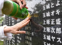 A woman who visited the Cornerstone of Peace, which commemorates the lives of people who died in the Battle of Okinawa during the Pacific War, pours tea on the name of a relative engraved on the wall, and touches it, in a process she repeated, at Okinawa Peace Memorial Park in the city of Itoman, Okinawa Prefecture, on June 23, 2021. (Mainichi/Yoshiyuki Hirakawa)