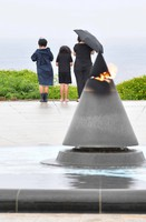 A family pays tribute to those who lost their lives in the Battle of Okinawa during the Pacific War in front of the sea at Okinawa Peace Memorial Park in the city of Itoman, Okinawa Prefecture, on June 23, 2021. The mother commented,