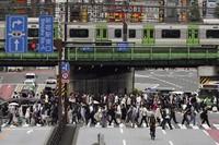 People walk along a pedestrian crosswalk in Tokyo, on June 22, 2021. (AP Photo/Eugene Hoshiko)