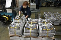 In this June 18, 2021, file photo, a worker packs copies of the Apple Daily newspaper at a printing house in Hong Kong. (AP Photo/Kin Cheung)