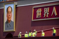 Workers prepare a raised seating area near a large portrait of Chinese leader Mao Zedong on Tiananmen Gate near Tiananmen Square in Beijing, on June 22, 2021. (AP Photo/Mark Schiefelbein)