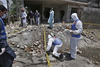 Investigators collect evidence at the site of explosion in Lahore, Pakistan, on June 23, 2021. (AP Photo/K.M. Chaudary)