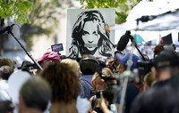 A portrait of Britney Spears looms over supporters and media members outside a court hearing concerning the pop singer's conservatorship at the Stanley Mosk Courthouse on June 23, 2021, in Los Angeles. (AP Photo/Chris Pizzello)