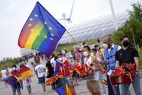 Football supporters are seen with LGBT pride flags outside of the stadium before the Euro 2020 soccer championship group F match between Germany and Hungary at the Allianz Arena in Munich, Germany, on June 23, 2021. (AP Photo/Matthias Schrader)