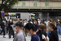 People wearing protective masks to help curb the spread of the coronavirus walk along a pedestrian crossing on June 24, 2021, in Tokyo. (AP Photo/Eugene Hoshiko)