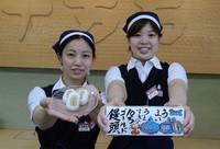 """Store staffers hold up """"Juman Gold Manju"""" buns produced by Jumangoku Fukusaya Co., in Saitama's Midori Ward. (Mainichi/Mineichiro Yamakoshi) =Click/tap photo for more images."""