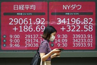 A woman wearing a protective mask walks in front of an electronic stock board showing Japan's Nikkei 225 and New York Dow indexes at a securities firm June 25, 2021, in Tokyo. (AP Photo/Eugene Hoshiko)