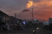 Motorists ride past as Mount Merapi looms in the background, in Sleman, Indonesia, on June 25, 2021. (AP Photo/Slamet Riyadi)