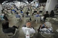 In this June 6, 2021, file photo, local residents wait for receiving the Moderna coronavirus vaccine at a mass vaccination center in Yokohama, near Tokyo. (AP Photo/Eugene Hoshiko)