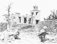 U.S. soldiers are seen watching a church where Japanese forces were hiding, in what is now the city of Naha, Okinawa Prefecture, in 1945. (Photo courtesy of the Okinawa Prefectural Archives)