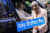 Ron Isley, left, and Ernie Isley pose for a photo with the street sign dedicated to them during a street renaming ceremony, on June 24, 2021, in Teaneck, N.J. (AP Photo/Mary Altaffer)