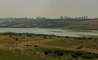 With Istanbul's skyline far in the distance a view of the Sazlidere dam, near the construction site for the first bridge of the Kanal Istanbul project, Thursday, June 24, 2021. (AP Photo/Emrah Gurel)