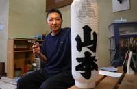 Osamu Onda is seen holding a hand-drawn chochin lantern in Tokyo's Taito Ward on May 26, 2021. (Mainichi/Yuki Miyatake)