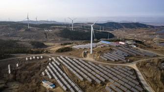中国の太陽光パネルと風力発電機。広大な国土は再エネ導入にも有利だ(中国甘粛省) (Bloomberg)