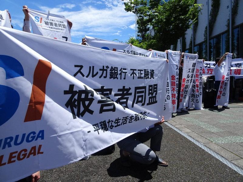 Pembeli memegang spanduk di depan venue setelah rapat umum pemegang saham Bank Suruga = Difoto oleh Makoto Imazawa pada 29 Juni 2021 di Kota Numazu, Prefektur Shizuoka