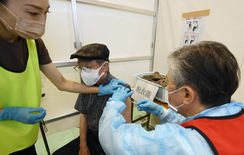 大阪市が運営する集団接種会場で新型コロナウイルスのワクチン接種を受ける男性(中央)=同市都島区の都島スポーツセンターで2021年5月24日午後1時28分、藤井達也撮影