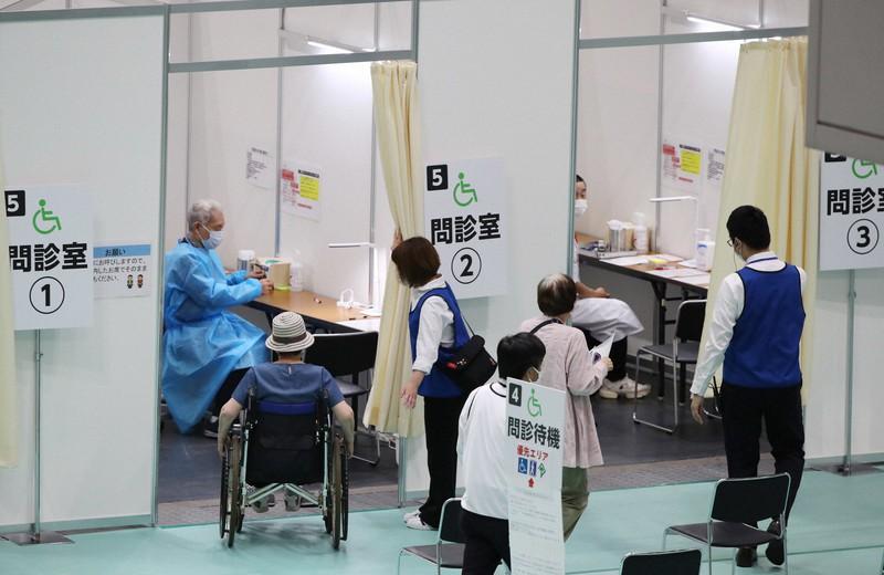 大阪市が設置した新型コロナウイルスワクチンの「大規模接種会場」で問診室に入る人たち=大阪市住之江区で2021年6月7日午前10時11分、梅田麻衣子撮影