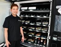 "Shinya Wada, president of Shinei Farm, stands in front of a vending machine selling ""tori-sashi"" in Minamikyushu, Kagoshima Prefecture, on May 25, 2021. (Mainichi/Junko Adachi)"