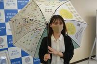 A woman is seen holding an umbrella illustrated with a map of the Ikaho hot spring resort, in Shibukawa, Gunma Prefecture, on June 28, 2021. (Mainichi/Tetsuya Shoji)