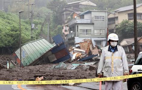A police officer blocks off an area near broken structures swept along by a massive mudslide in Atami, Shizuoka Prefecture, on July 3, 2021. (Mainichi/Kentaro Ikushima)