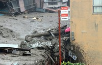 A car is seen crushed by a massive mudslide in Atami, Shizuoka Prefecture, on July 3, 2021. (Mainichi/Kentaro Ikushima)