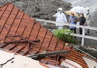 Police officers and others inspect property damage after a massive mudslide in Atami, Shizuoka Prefecture, on July 3, 2021. (Mainichi/Natsuki Nishi)