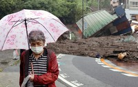 A woman stands near the devastation wrought on her neighborhood of Atami, Shizuoka Prefecture, by a massive mudslide on July 3, 2021. Her own house escaped damage. (Mainichi/Kentaro Ikushima)
