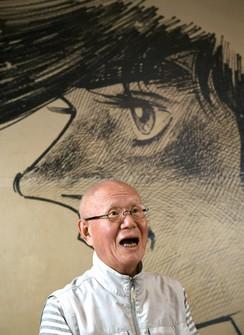 "This July 2020 file photo shows Tetsuya Chiba. In the background is an illustration of Joe Yabuki, the main character of his manga series ""Ashita no Joe."" (Mainichi/Kimi Takeuchi)"