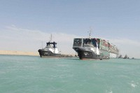 In this March 29, 2021, file photo released by the Suez Canal Authority, the Ever Given, a Panama-flagged cargo ship is accompanied by Suez Canal tugboats as it moves in the Suez Canal, Egypt. (Suez Canal Authority via AP)