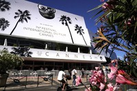 People walk in front of the Palais des Festival prior to the 74th international film festival, in Cannes, southern France, on July 5, 2021. (AP Photo/ Brynn Anderson)