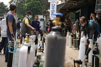 People queue up to refill their oxygen tanks at a filling station in Jakarta, Indonesia, on July 5, 2021. (AP Photo/Dita Alangkara)