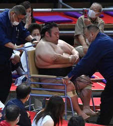 Ozeki Takakeisho is seen seated in a wheelchair after injuring his neck in a second-day bout against rank-and-filer Ichinojo at Dophins Arena in Nagoya, on July 5, 2021. (Mainichi)