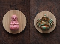 """A """"jizo-bosatsu"""" kake-botoke painted soft pink, left, and a """"1,000-armed bodhisattva of compassion"""" kake-botoke with a special paint that makes it look old are seen in this combination photo provided by Shun Nakamura."""
