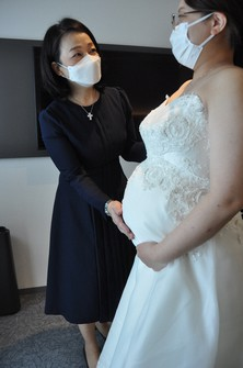 A woman, right, is seen wearing a maternity bridal gown in a way her body shape is expected to be in at the time of her wedding, in Nagoya's Nakamura Ward on June 21, 2021. (Mainichi/Sanami Kato)