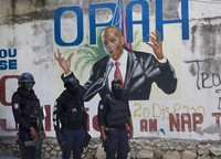 Police stand near a mural featuring Haitian President Jovenel Moise, near the leader's residence where he was killed by gunmen in the early morning hours, in Port-au-Prince, Haiti, on July 7, 2021. (AP Photo/Joseph Odelyn)