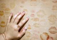 Strip show dancer Yukina is seen touching the lipstick stain she left on a wall inside the Hiroshima Daiichi Gekijyou in the city's Naka Ward before her final performance on the day the theater closed, in this May 2021 photo. The wall is said to have been left with kiss marks by retiring dancers for around 30 years. (Mainichi/Naohiro Yamada)