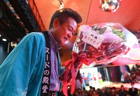 Yoshitaka Fukuo, president of Hiroshima Daiichi Gekijyou strip show theater, holds a bouquet given to him by dancers after delivering a speech before the theater's closure, as seen in this May 2021 photo taken in the city's Naka Ward. (Mainichi/Naohiro Yamada)