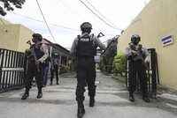 Police officers stand guard at a local police hospital to which the bodies of militants killed during a raid were taken to, in Palu, Central Sulawesi, Indonesia, on July 11, 2021. (AP Photo/Josua Marunduh)