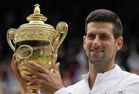Serbia's Novak Djokovic holds the winner's trophy as he poses for photographers after he defeated Italy's Matteo Berrettini in the men's singles final on day thirteen of the Wimbledon Tennis Championships in London, on July 11, 2021. (AP Photo/Kirsty Wigglesworth)