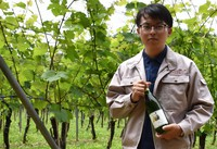 "An employee at Sun Mamoru Winery Inc. shows the ""Danger"" wine bottle at Schonburger vineyard in Mutsu, Aomori Prefecture, on July 7, 2021. (Mainichi/Yushi Ezawa)"