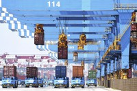 In this June 4, 2021 file photo, gantry cranes move containers onto transporters at a port in Qingdao in eastern China's Shandong province. (Chinatopix via AP)