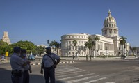 Police stand guard near the National Capitol building in Havana, Cuba, on July 12, 2021, the day after protests against food shortages and high prices amid the coronavirus crisis. (AP Photo/Ismael Francisco)