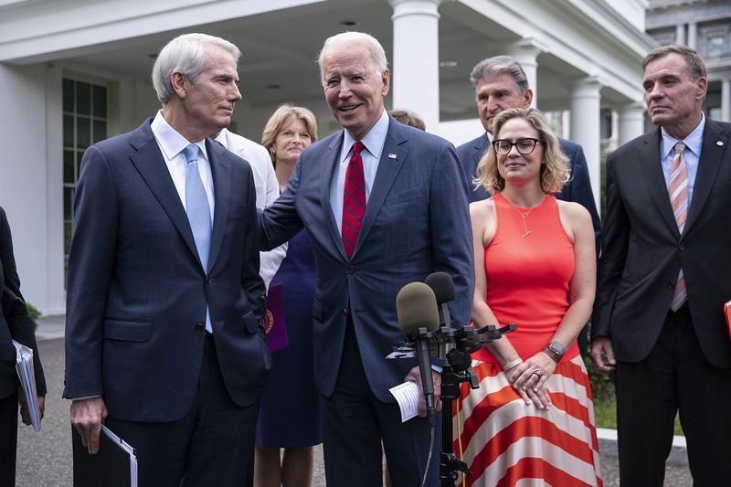インフラ投資の合意を喜ぶバイデン大統領(中央)と共和党のロブ・ポートマン上院議員(左)ら超党派議員 (Bloomberg)